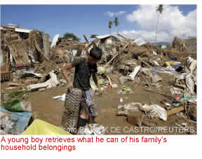 A young boy retrieves what he can of his family's household belongings