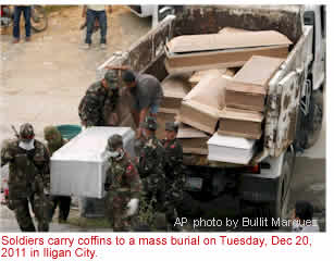 Soldiers carry coffins to a mass burial on Tuyesday, Dec 20, 2011 in Iligan City
