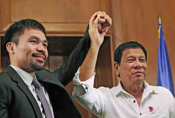 President Rodrigo Duterte raises the hand of Sen. Manny Pacquiao during a courtesy call at Malaca�an in December 2016.
